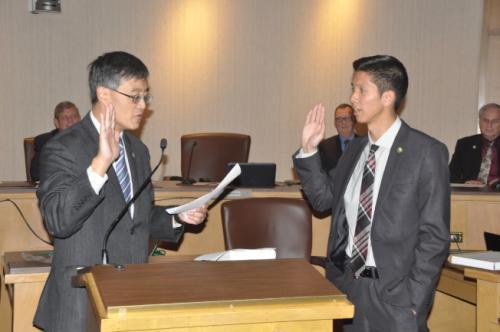中国侨网方友明(右)在前市长李洲晓与父母的见证下宣誓,成为桑市史上第三位亚裔市议员,也是桑市历年来最年轻的市议员。(美国《世界日报》/林亚歆 摄)